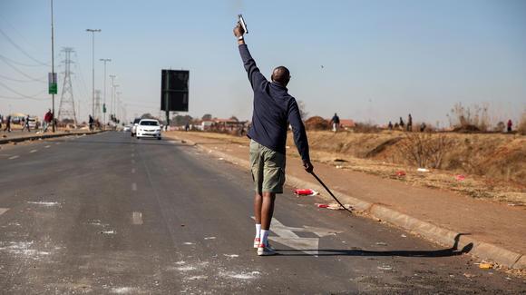 Un vigilante dispara su arma para dispersar a los saqueadores el 14 de julio de 2021 en Johannesburgo, Sudáfrica.